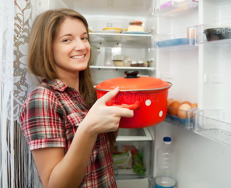冰箱女孩平底锅放置 免版税库存照片