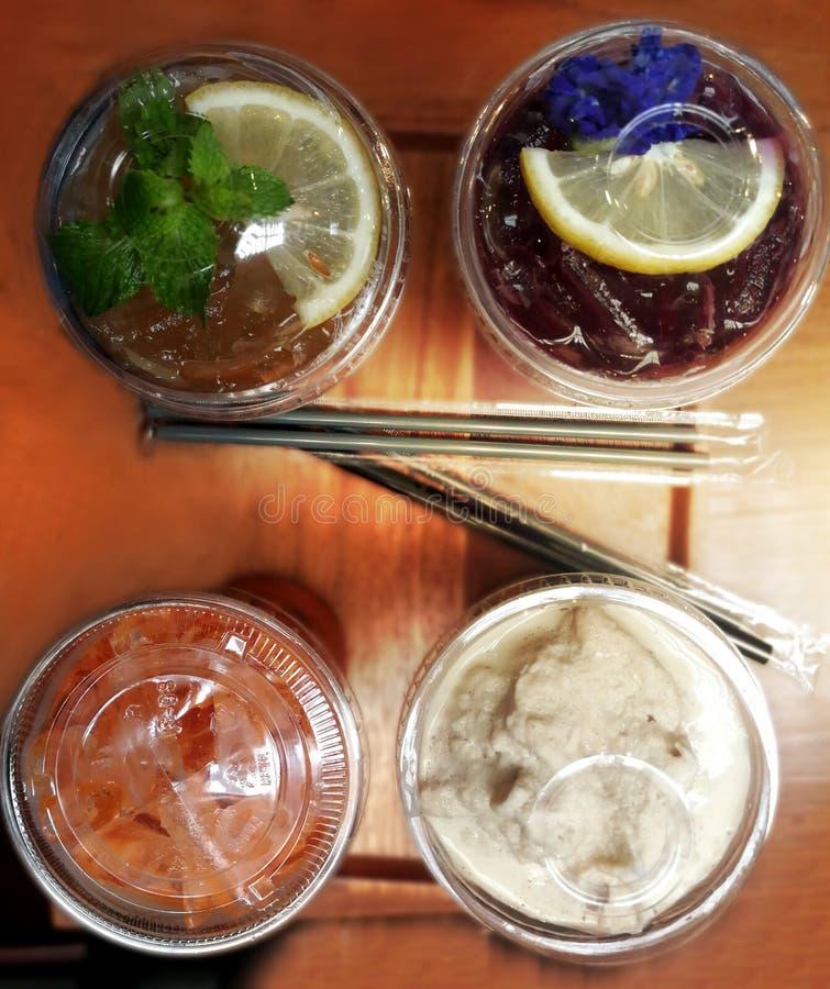 冰茶、蝴蝶豌豆汁用蜂蜜和石灰,柠檬茶和咖啡在木桌上震动 库存图片