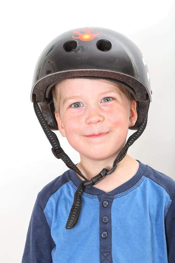 头戴黑冰鞋盔甲的微笑的白肤金发的男孩 免版税库存照片