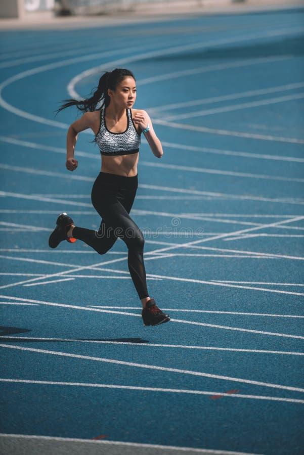 冲刺在连续轨道体育场的年轻女运动员 免版税库存照片