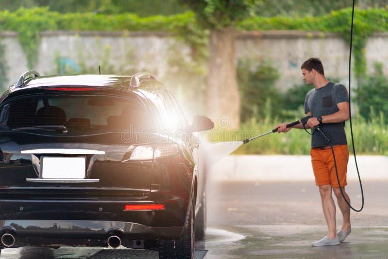 冲洗肥皂suds的年轻人他的汽车 库存图片