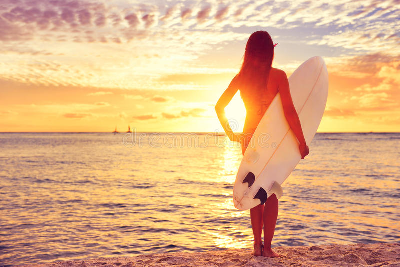 冲浪冲浪者的女孩看海洋海滩日落 免版税图库摄影