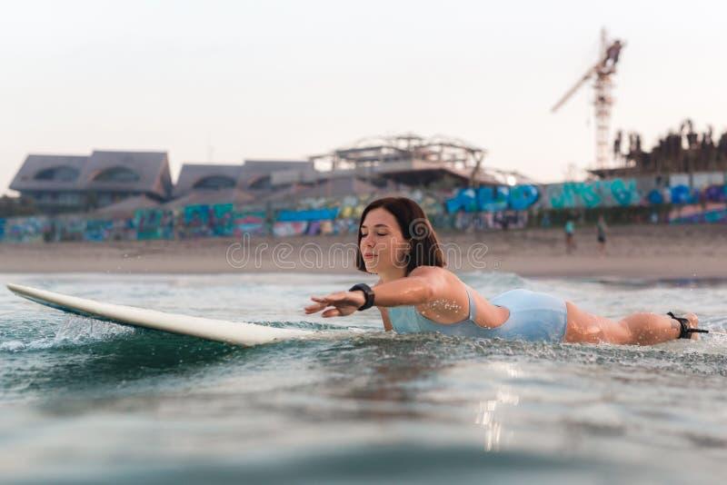 冲浪在一个委员会的明亮的比基尼泳装的少妇在海洋 库存照片