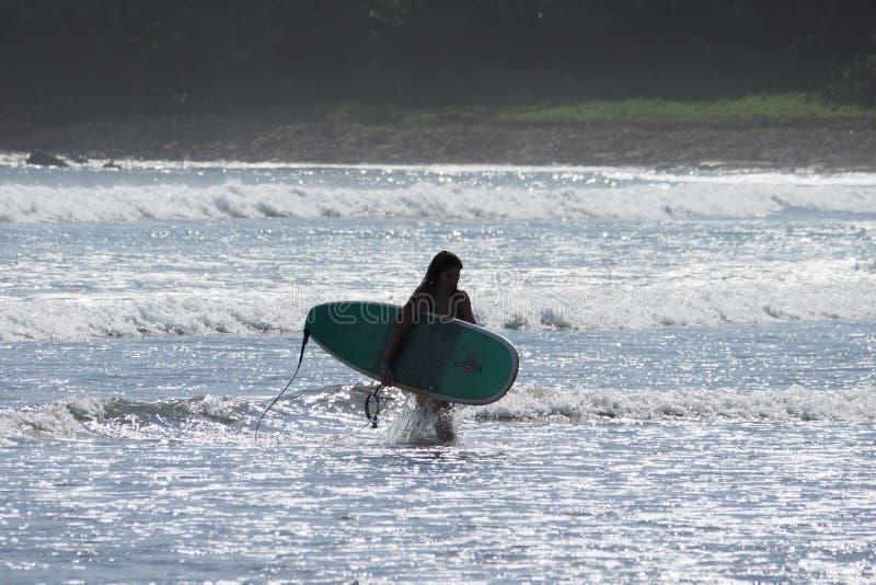 冲浪在尼加拉瓜的年轻女人 免版税库存图片