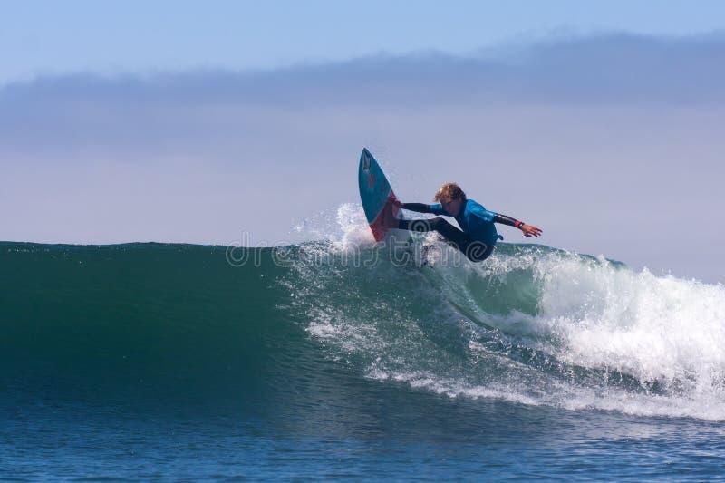 冲浪在波浪的男孩在圣克鲁斯加利福尼亚 库存照片
