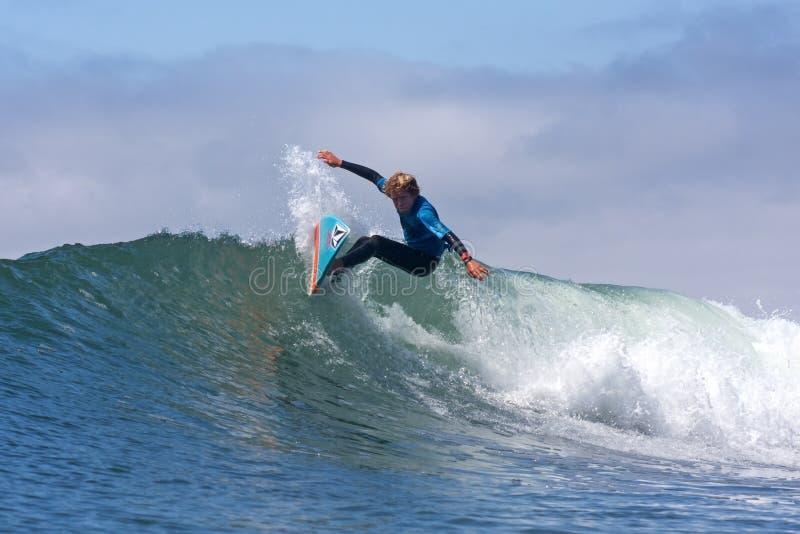 冲浪在波浪的男孩在圣克鲁斯加利福尼亚 库存图片