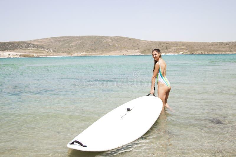 冲浪在海洋的冲浪者妇女 图库摄影