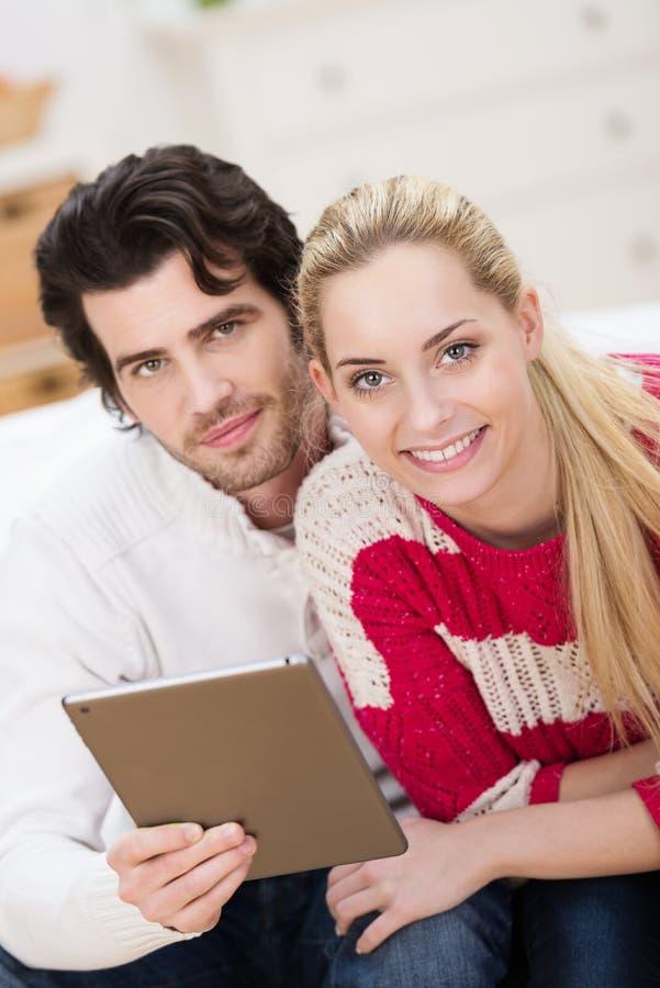 冲浪在片剂个人计算机上的年轻夫妇万维网 库存图片
