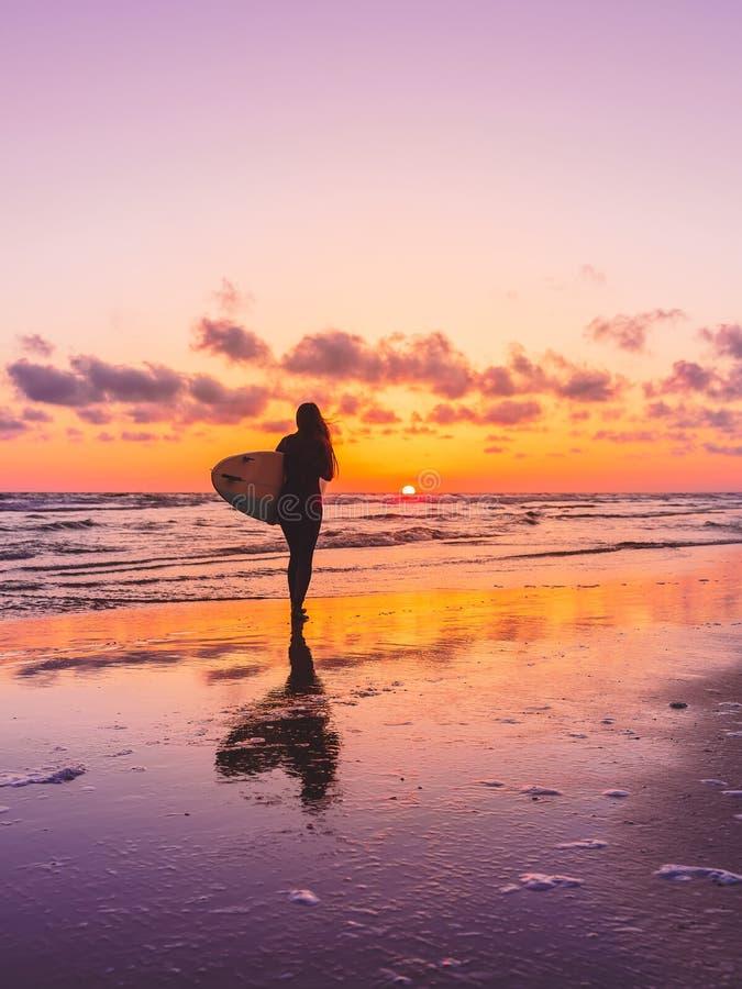 冲浪有冲浪板的妇女在海滩在日落或日出 库存图片