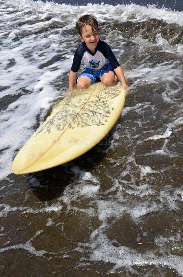 冲浪板的小孩男孩 免版税库存图片
