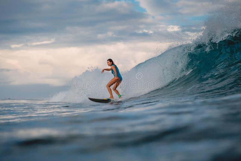 冲浪板的海浪女孩 妇女在冲浪期间的海洋 冲浪者和波浪 库存图片