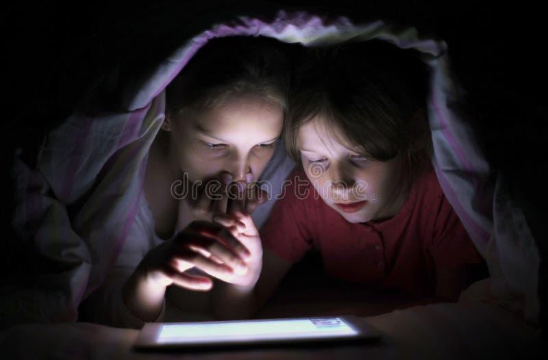 冲浪片剂的微笑的女孩在毯子下在晚上 免版税图库摄影
