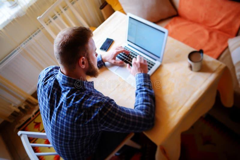 冲浪网在办公室 研究膝上型计算机和微笑,当坐在他的工作地点的确信的年轻人在办公室时 库存照片