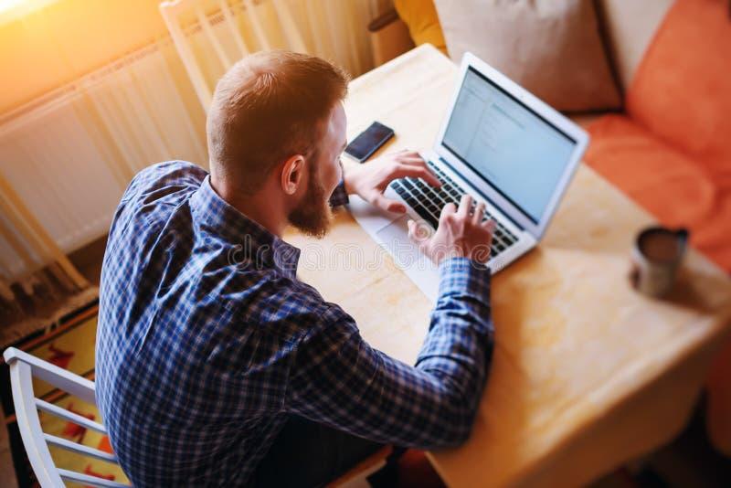 冲浪网在办公室 研究膝上型计算机和微笑,当坐在他的工作地点的确信的年轻人在办公室时 库存图片