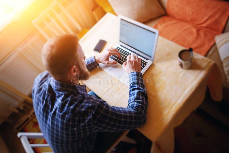 冲浪网在办公室 研究膝上型计算机和微笑,当坐在他的工作地点的确信的年轻人在办公室时 免版税库存图片