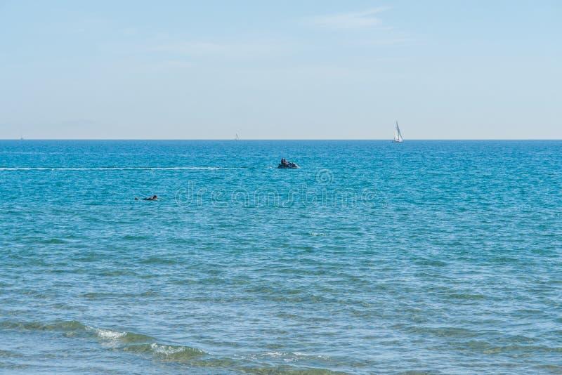 冲浪者、喷气机滑雪和游艇在地中海有清楚的大海的在一个晴朗的夏日在La Zenia 免版税库存照片