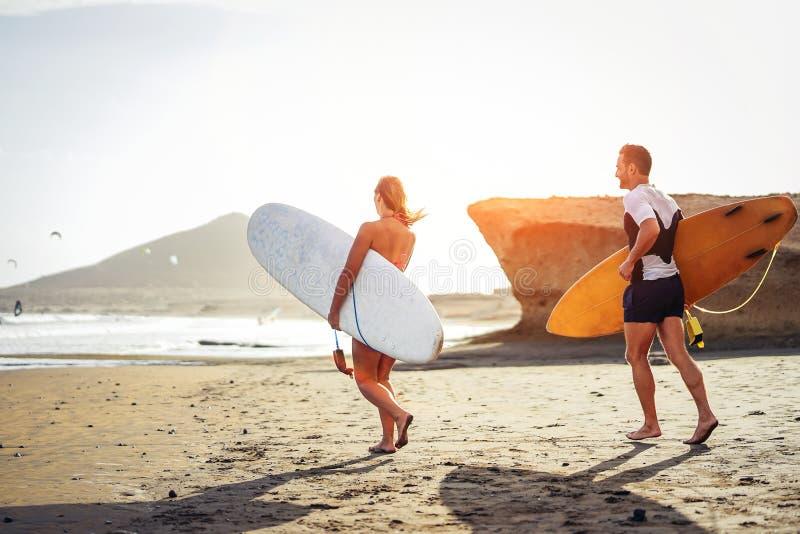 冲浪者与冲浪板一起的夫妇赛跑在日落的海滩-获得运动的朋友去的乐趣冲浪 库存图片
