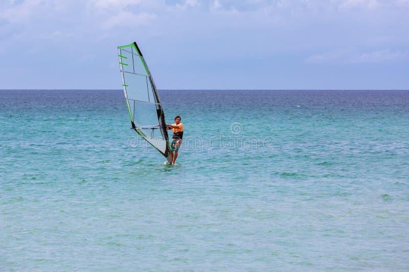 冲浪者乘坐的波浪在一美好的好日子 享受风和海洋冲浪的年轻人 库存照片