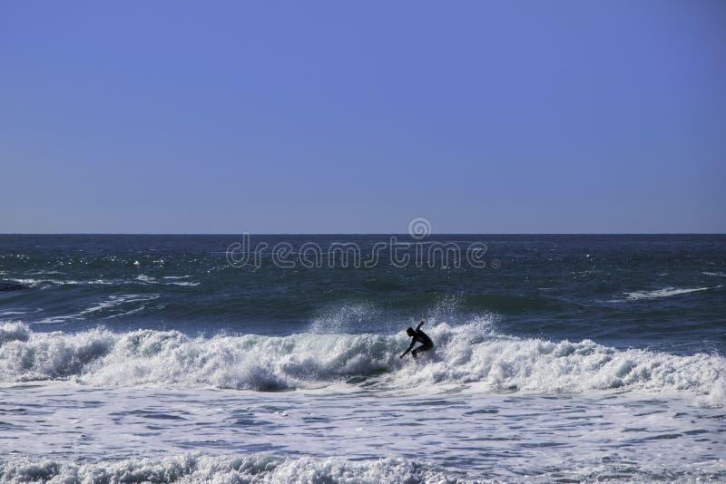 冲浪者乘驾挥动在Trebarwith子线在康沃尔郡,英国 免版税图库摄影