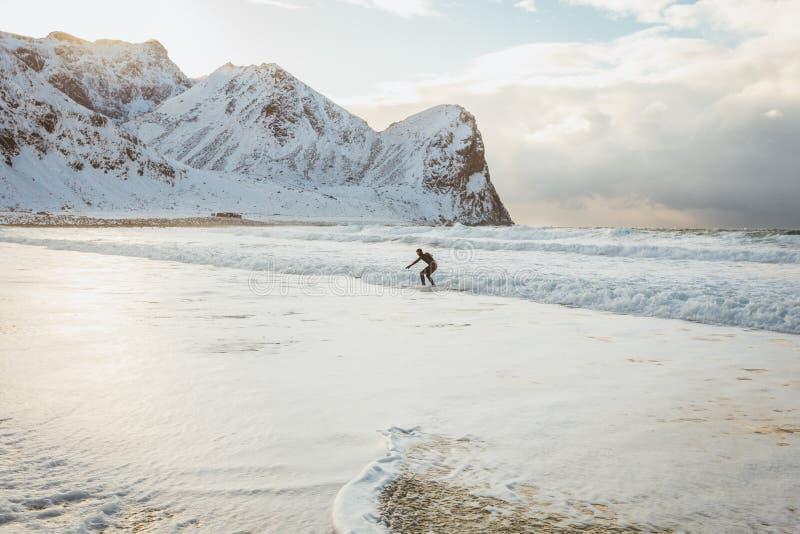 冲浪者在一冬天好日子征服海洋的波浪 免版税库存照片
