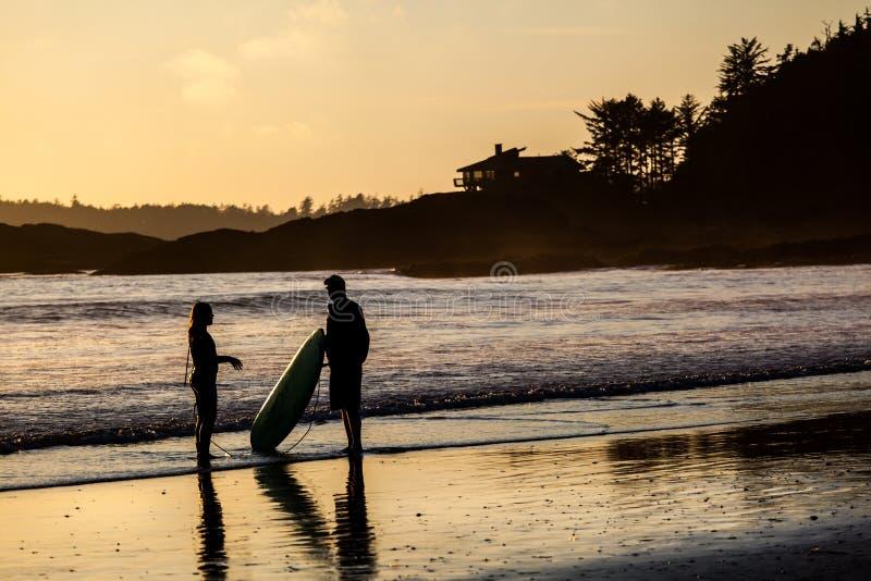 冲浪者夫妇Tofino海滩的在日落 免版税库存图片