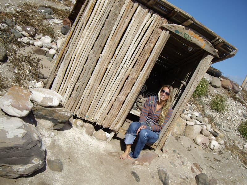 冲浪者女孩在被放弃的棚子,下加利福尼亚州坐 免版税库存图片