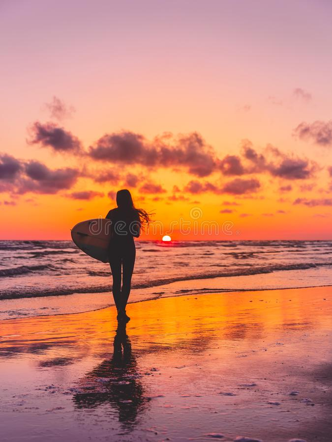 冲浪者女孩的剪影有冲浪板的在日落的一个海滩 冲浪者和海洋 免版税库存图片
