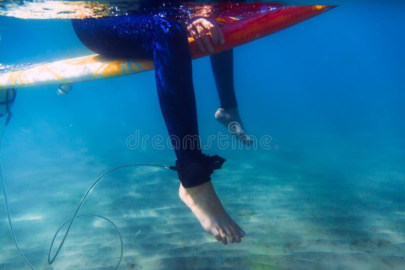 冲浪者妇女坐冲浪板,在水面下 冲浪者和海洋 库存照片