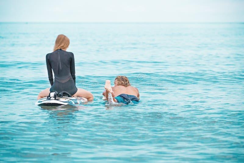 冲浪者海滩微笑的夫妇的冲浪者走在海滩和获得乐趣在夏天 极限运动和 图库摄影