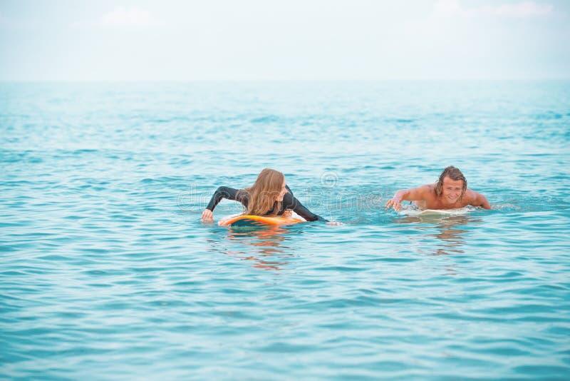 冲浪者海滩微笑的夫妇的冲浪者走在海滩和获得乐趣在夏天 极限运动和 免版税库存照片