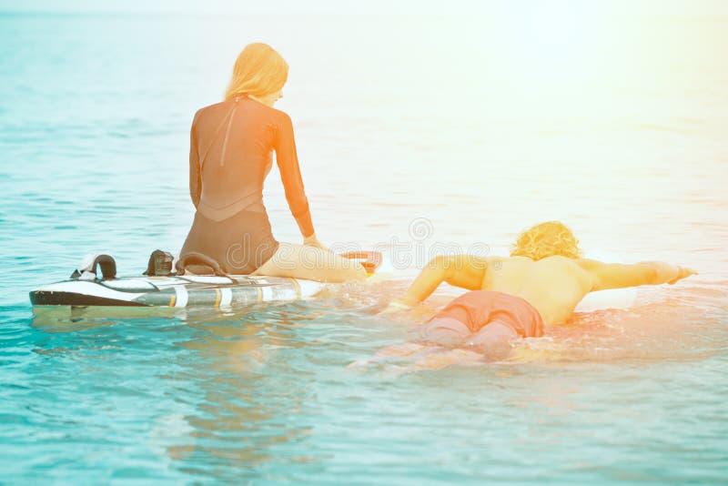 冲浪者海滩微笑的夫妇的冲浪者走在海滩和获得乐趣在夏天 极限运动和 免版税图库摄影