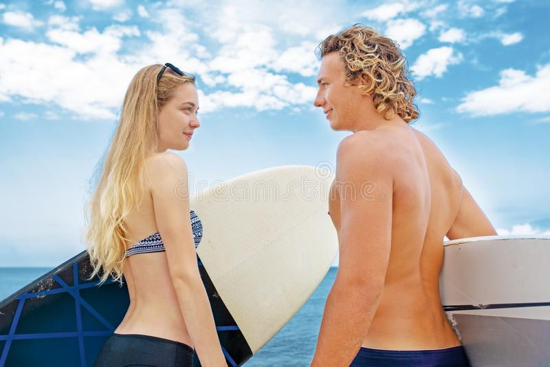 冲浪者海滩微笑的夫妇的冲浪者走在海滩和获得乐趣在夏天 极限运动和 库存图片
