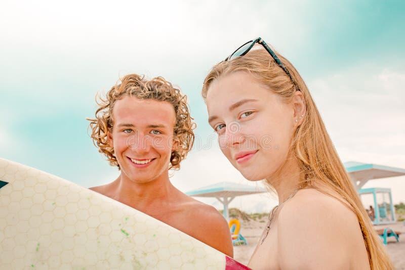 冲浪者海滩微笑的夫妇的冲浪者走在海滩和获得乐趣在夏天 极限运动和 免版税库存图片