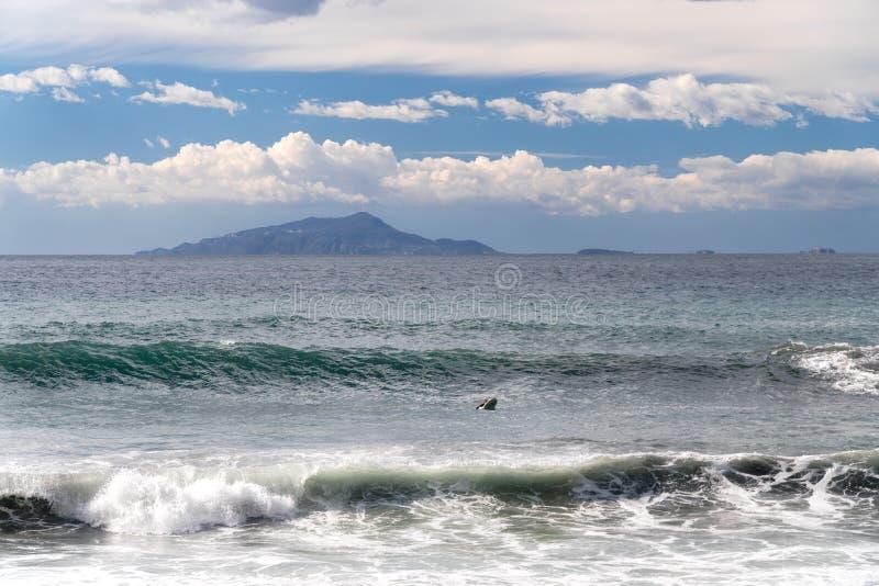 冲浪者采取波浪,在冲浪板,沿波浪的幻灯片,在山的背景中,索伦托意大利 免版税库存照片