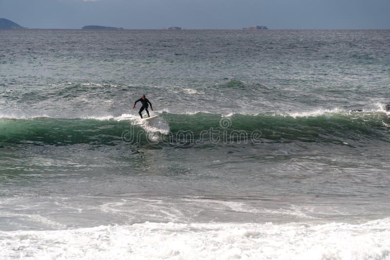 冲浪者采取波浪,在冲浪板,沿波浪的幻灯片,在山的背景中,索伦托意大利 免版税库存图片