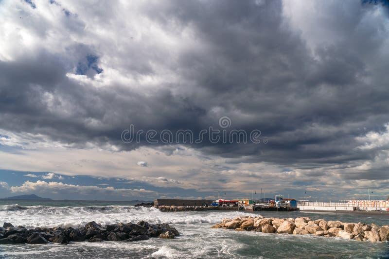 冲浪者采取波浪,在冲浪板,沿波浪的幻灯片,在山的背景中,索伦托意大利 免版税图库摄影