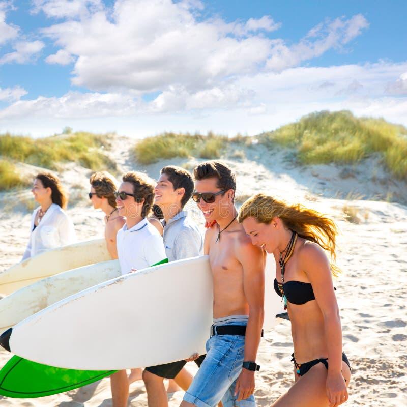冲浪者青少年的男孩和女孩编组走在海滩 免版税图库摄影