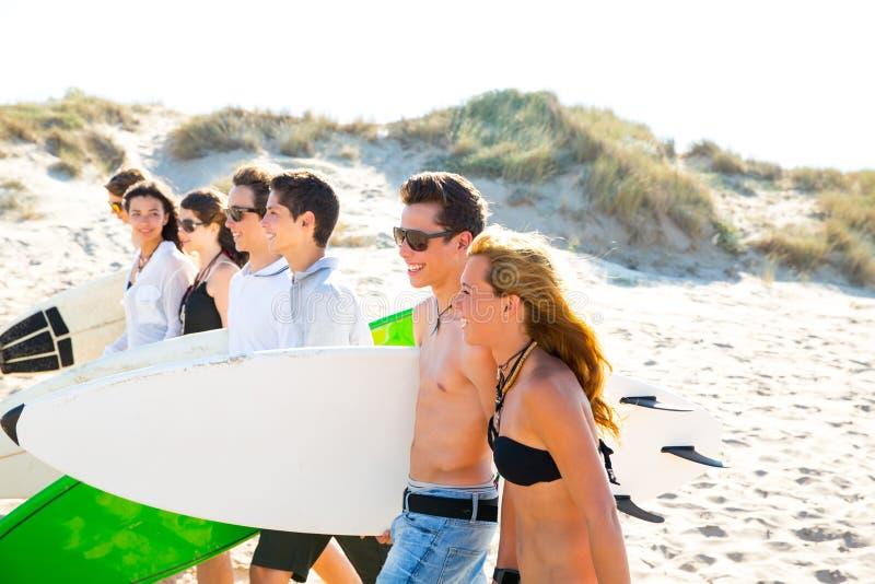 冲浪者青少年的男孩和女孩编组走在海滩 库存图片