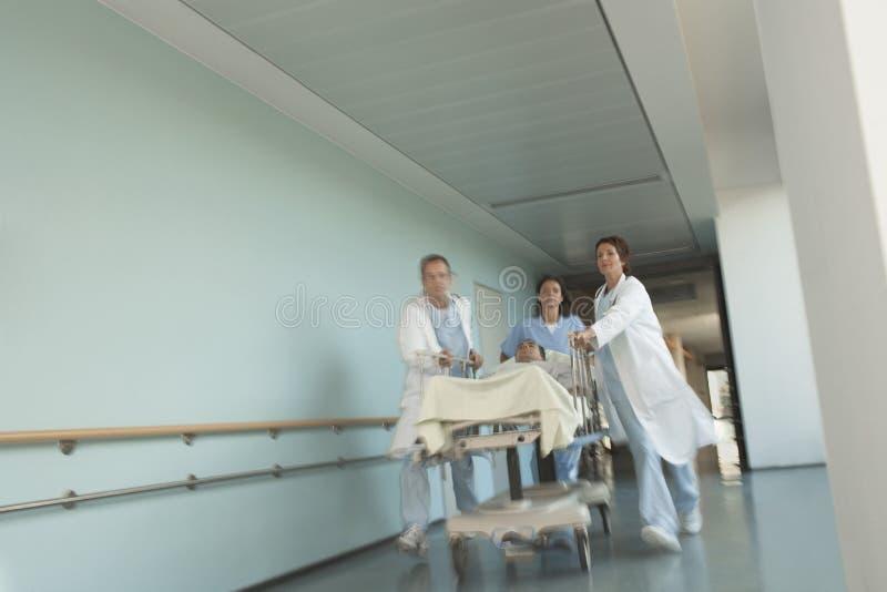 冲盖尼式床下来医院走廊的医师患者 免版税图库摄影
