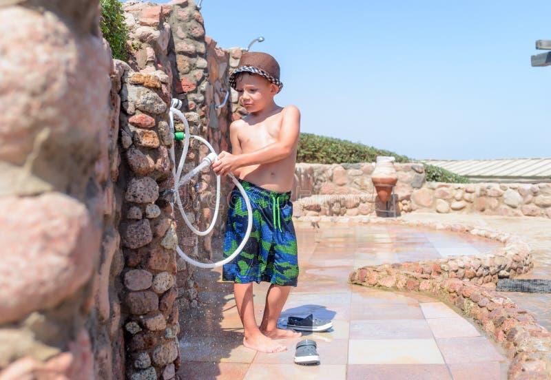 冲洗用水管的微笑的愉快的年轻男孩 库存图片