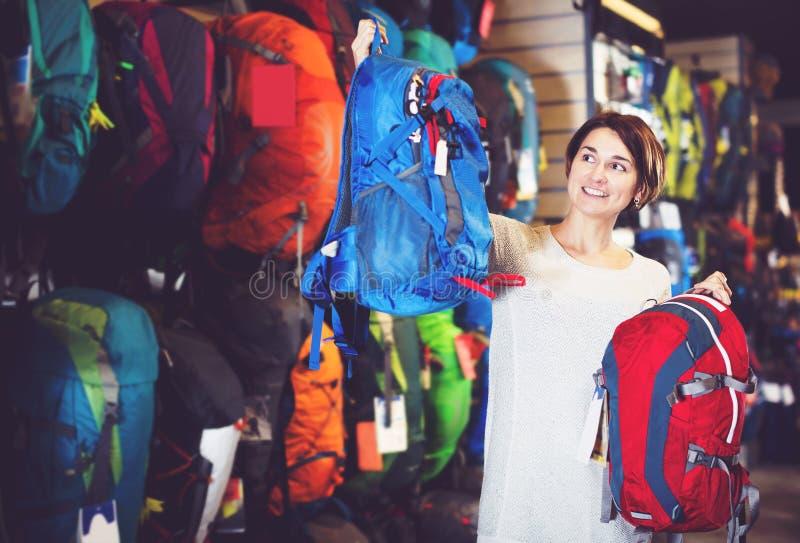 决定新的背包的女性顾客 免版税库存图片