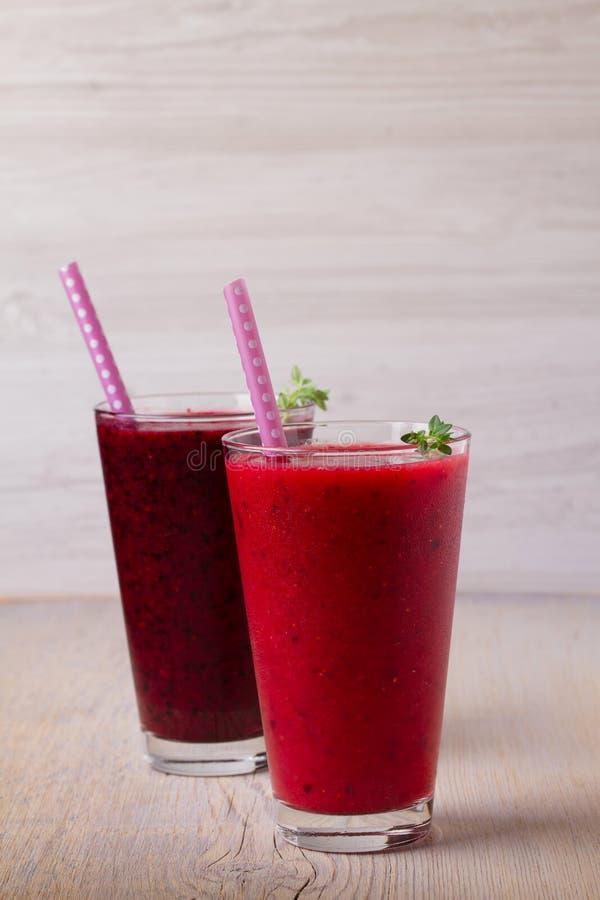 冷冻夏天莓果圆滑的人:蓝莓、草莓、莓、蔓越桔、无核小葡萄干和黑莓在木backgroun 免版税库存照片