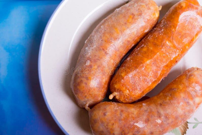 冷冻猪肉香肠宏指令在板材的 免版税库存图片