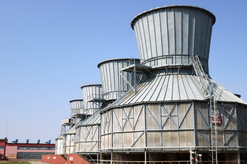 冷却的循环水的大灰色冷却塔,连续站立在炼油厂,石油化学制品,化学制品 免版税库存图片