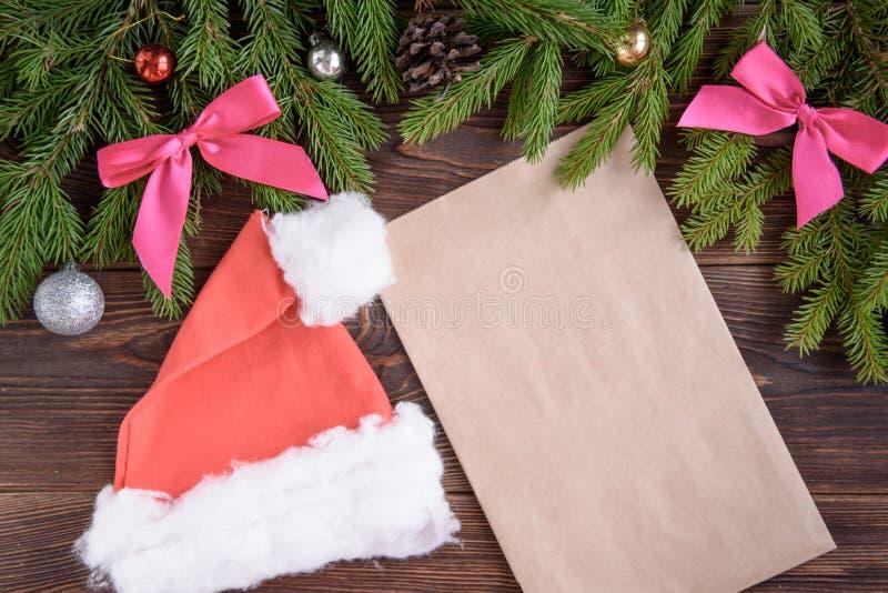 冷杉分支、桃红色丝带弓、圣诞节盖帽、信封和圣诞节球 背景新年度 库存图片