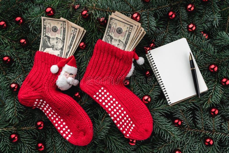 冷杉分支背景  与金钱的圣诞老人的红色长袜 袋子看板卡圣诞节霜klaus ・圣诞老人天空 顶视图 Xmas祝贺 3d购物车被生成的图象购物 免版税库存图片