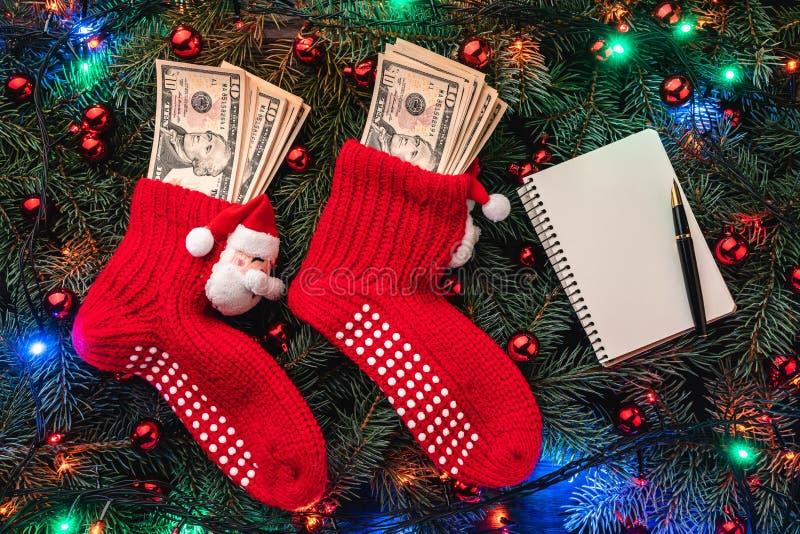 冷杉分支背景  与金钱的圣诞老人的红色长袜 袋子看板卡圣诞节霜klaus ・圣诞老人天空 顶视图 Xmas祝贺 免版税图库摄影