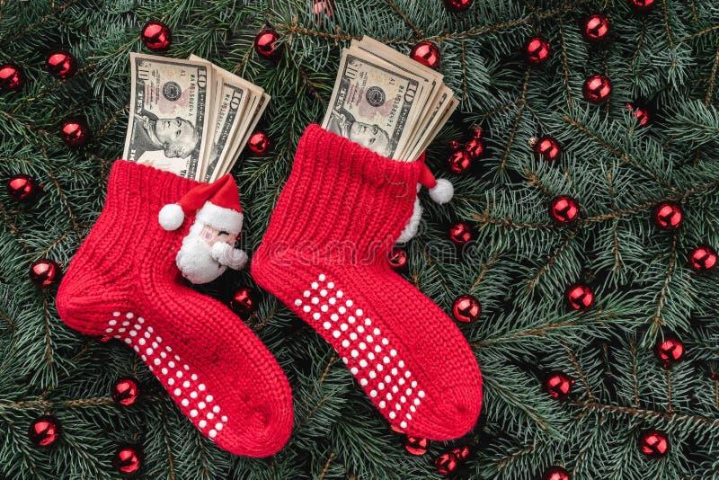 冷杉分支背景  与金钱的圣诞老人的红色长袜 袋子看板卡圣诞节霜klaus ・圣诞老人天空 顶视图 Xmas祝贺 免版税库存照片