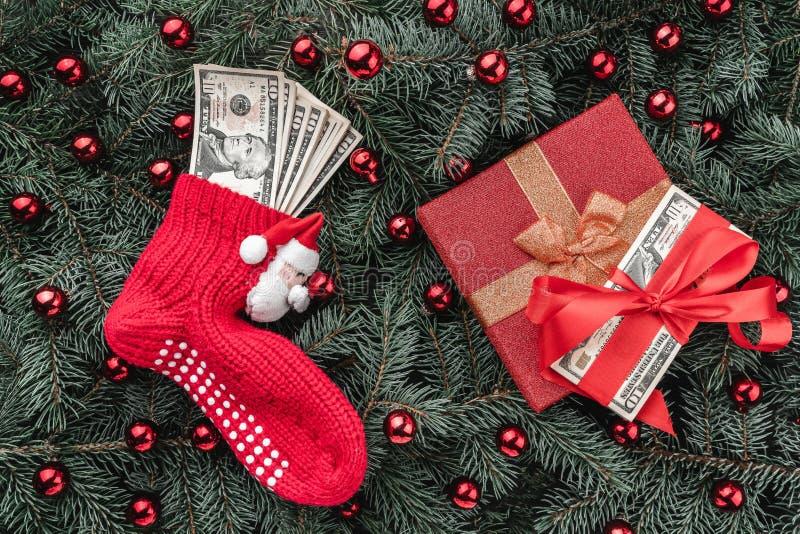 冷杉分支背景  礼物,金钱 与金钱的圣诞老人的红色袜子 袋子看板卡圣诞节霜klaus ・圣诞老人天空 顶视图 Xmas祝贺 库存照片