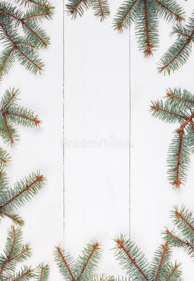 冷杉分支以框架的形式在白色木桌上的 圣诞节和新年快乐构成 平的位置,上面 库存照片